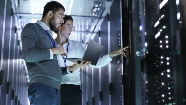 Looped Cinemagraph: Male and Female IT Engineers Standing in the Working Data Center with Server Racks LED Lights Blinking. Looped Cinemagraph: Male and Female IT Engineers Standing in the Working Data Center with Server Racks LED Lights Blinking. Shot on RED EPIC-W 8K Helium Cinema Camera. network server stock videos & royalty-free footage