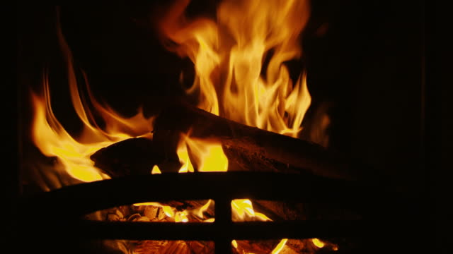 Looping fireplace with real flames and burning logs. Ideal for winter screensaver in 4K