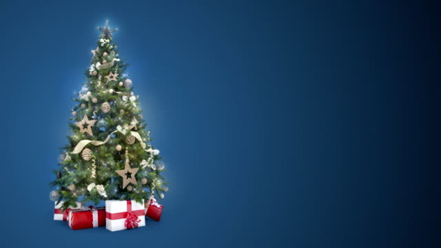 ライトをループすると、ロゴやコピーを配置するテキスト領域に青色の背景色のギフト用の箱のクリスマス ツリーが飾られています。アニメーションの抽象クリスマス グリーティング ポスト カードをプレゼント。4 k のシームレスなループ動画 - クリスマスツリー点の映像素材/bロール