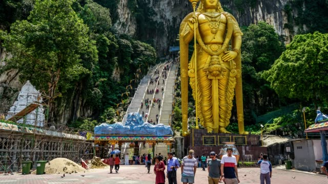 vídeos de stock e filmes b-roll de lord murugan hindu deity statue at batu caves and tourist flow in malaysia time lapse 4k - hinduísmo