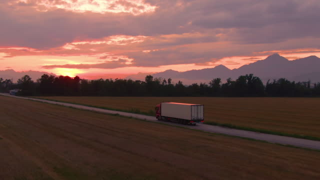 DRONE: Lorry drives goods towards a logistics center on a sunny summer evening.