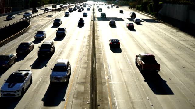 vidéos et rushes de navetteurs de freeway de los angeles en automobiles route de rétro-éclairé - californie du sud