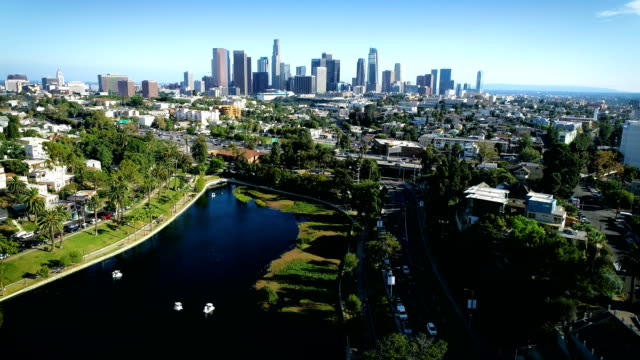 Los Angeles skyline cityscape Downtown Perfect city view of the Iconic West Coast City backing up over Pond with Los Angeles skyline cityscape in the background - Los Angeles , California , USA aerial drone view 2019 above Echo Lake Park east stock videos & royalty-free footage