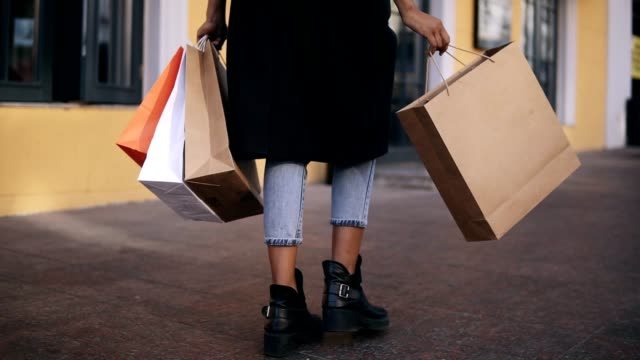 lose up of woman legs wearing stylish black coat and jeans at day time hold colored shopping bags after big shopping day. fashion shopper shopaholic in slow motion. rare view - borsa della spesa video stock e b–roll