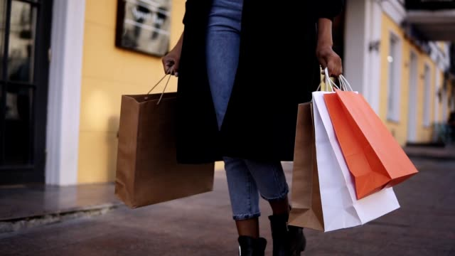 lose up of woman legs wearing stylish black coat and jeans at day time hold colored shopping bags after big shopping day. Fashion shopper shopaholic in slow motion video