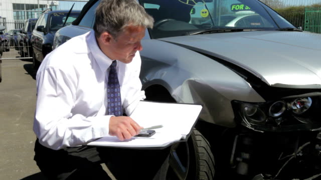 loss adjuster inspecting car involved in accident - insurance bildbanksvideor och videomaterial från bakom kulisserna