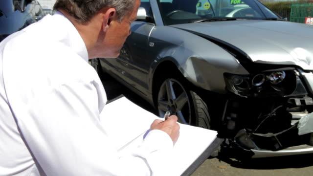 loss adjuster inspecting car involved in accident - försäkring bildbanksvideor och videomaterial från bakom kulisserna