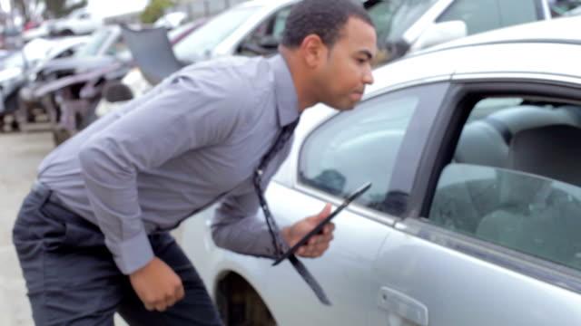 loss adjuster inspecting car wreck using digital tablet - försäkring bildbanksvideor och videomaterial från bakom kulisserna