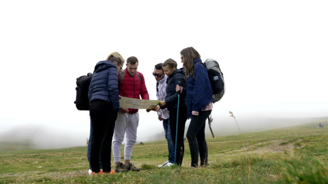 lost group of teenage friends checking the map trying to find out the right way on foggy mountain top - indicare la via video stock e b–roll