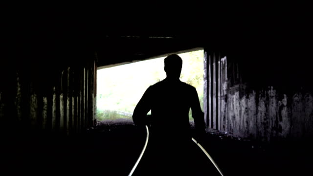 4K Lost man silhouette runs to dark tunnel exit. Back view. Abstract silhouette shot. Escape. Problems and depression