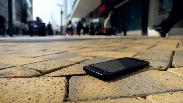 Lost smartphone. A lost smartphone lies on the ground. Many people walking past.  lost stock videos & royalty-free footage