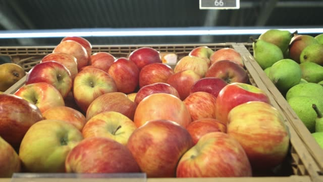 A lot of apples red and green. A bunch of apples lie in the supermarket, camera span
