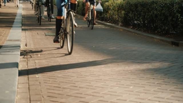 狭い通りに沿って車で自転車がたくさん。画像でホイールのみが表示されます、有名な人々 がないです。ヨーロッパにおける生態学的にクリーンな輸送 - サイクリング点の映像素材/bロール