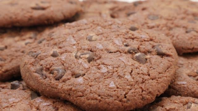 stockvideo's en b-roll-footage met veel chocolade koekjes smakelijke koekjes op stapelvoedsel achtergrond 4k - ongezond leven