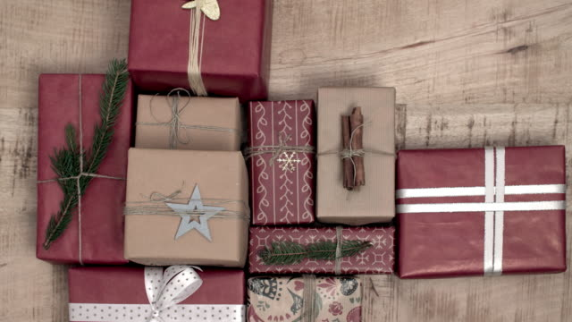 a lot of christmas presents on wooden background - gift filmów i materiałów b-roll
