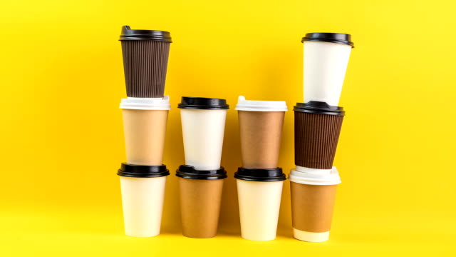 a lot of disposable cups for coffee and tea change places. nice catering for a coffee shop. video footage stop motion timelapse. bright yellow background. coffee take away ( to go ) - twórczy zawód filmów i materiałów b-roll