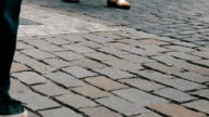 istock Lot of feet a crowd of people strolling along the cobbles of the city 871156348