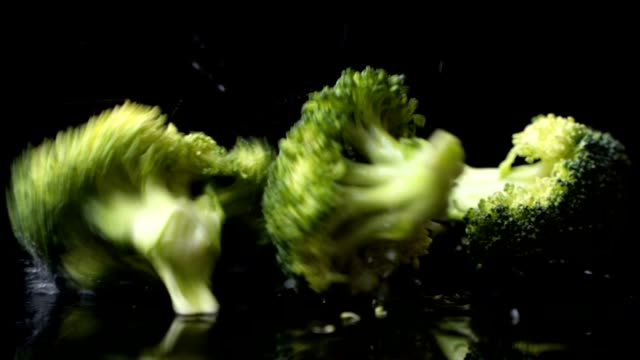 A lot of green fresh broccoli fall on a glass with splashes and drops of water in slow motion on a dark background. Ingredients for Salad, Healthy Food