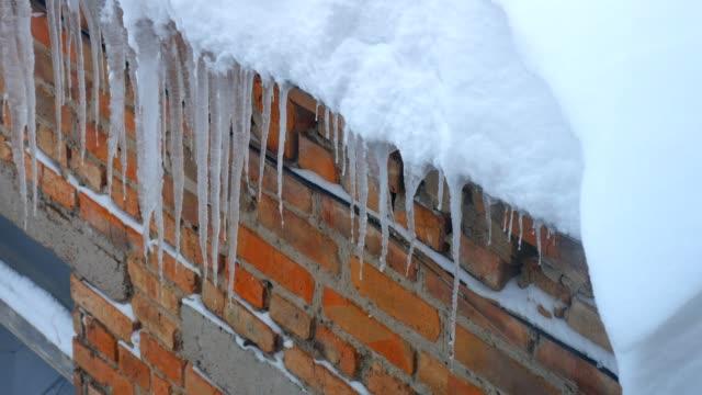 en hel del istappar hängande från ett tak på en bakgrund av en tegel vägg - icicle bildbanksvideor och videomaterial från bakom kulisserna