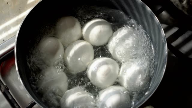 a lot of white eggs lie and boil in a metal pan in boiling water. close up. the view from the top. 4k. - bollente video stock e b–roll