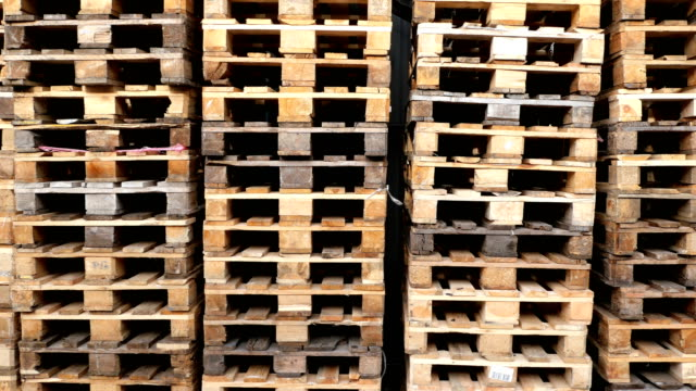 A lot stacks of used wooden pallets of euro type on warehouse is ready for recycling.