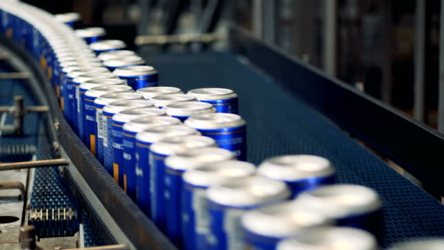 Lots of cans with beer on a factory conveyor, close up.