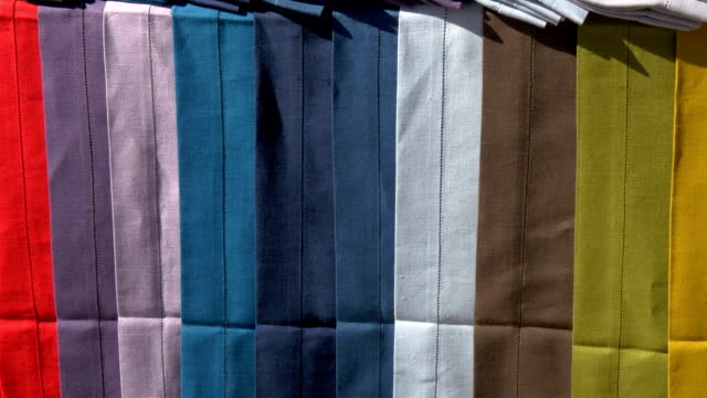 Lots of colorful cloth on display hanging on the table