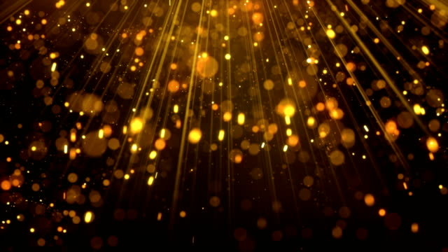 Lots of gold glitter particles falling in light rays loop video