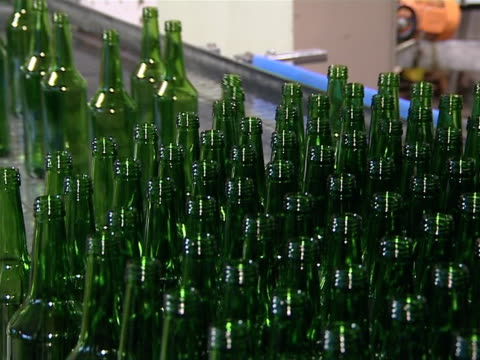 Lots of green bottle being prepared for packaging in factory. video