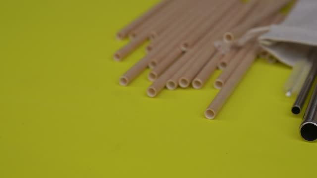 Lots of paper and stainless drinking straws on a yellow background. Alternatives to plastic drinking straws concept. Eco-friendly products concept