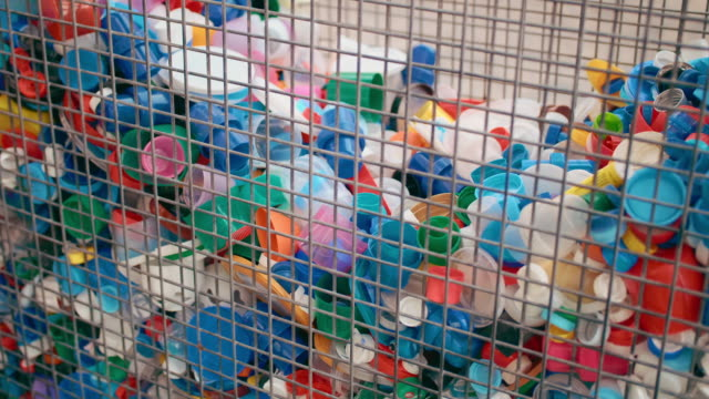 massor av plast kapsyler i en järnbur för att samla plast. begreppet insamling av plastavfall och skräp, naturvård, miljöförorening. teneriffa, kanarieöarna - recycling heart bildbanksvideor och videomaterial från bakom kulisserna