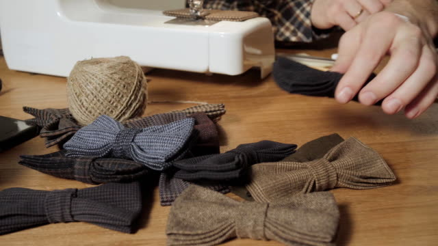準備した蝶蝶ネクタイ前景に、ウール製の多くは、完成した製品を追加します。良い若い男仕立て屋として働いて、染織工房でミシンを使ってします。 - 自家製点の映像素材/bロール
