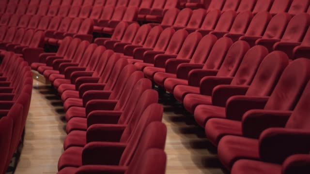 lots of red chairs in the theater - mebel do siedzenia filmów i materiałów b-roll