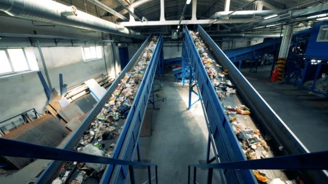 lots of trash go on two conveyors, top view. - odzyskiwanie i przetwarzanie surowców wtórnych filmów i materiałów b-roll
