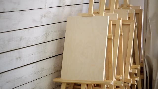 lots of wooden easels stand in corner of workshop - cavalletto attrezzatura per arti e mestieri video stock e b–roll