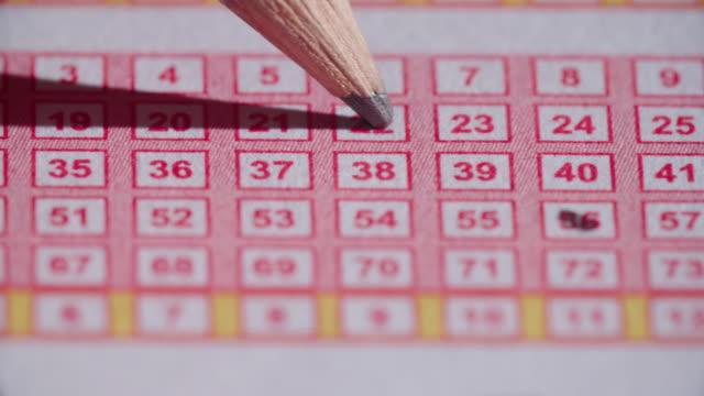 Billete de lotería lápiz en números a través de cierre para arriba - vídeo