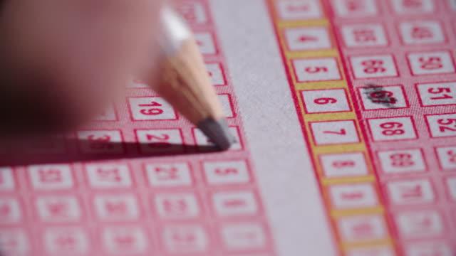 lottoschein bleistift in zahlen nach unten schließen sich - lotto stock-videos und b-roll-filmmaterial