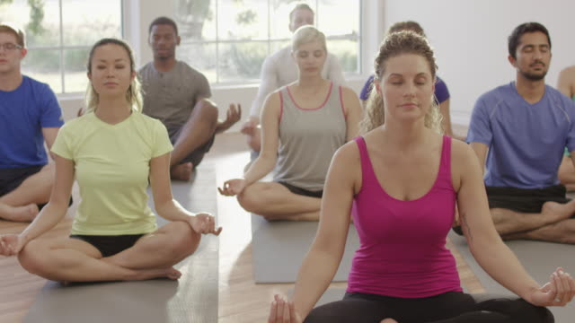 Lotus Position in Yoga Class A large group in a yoga class meditate in lotus position. lotus position stock videos & royalty-free footage