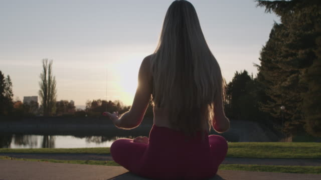 Lotus Yoga Pose Female Body Silhouette Long Haired Woman in Meditative State Facing the Sun - Lens Flare