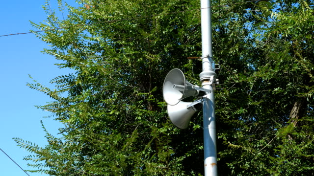Loudspeakers fitted to make announcements on the street pole. Loudspeakers fitted to make announcements on the street pole. In the background dense foliage of trees and blue sky. Close up. megaphone stock videos & royalty-free footage
