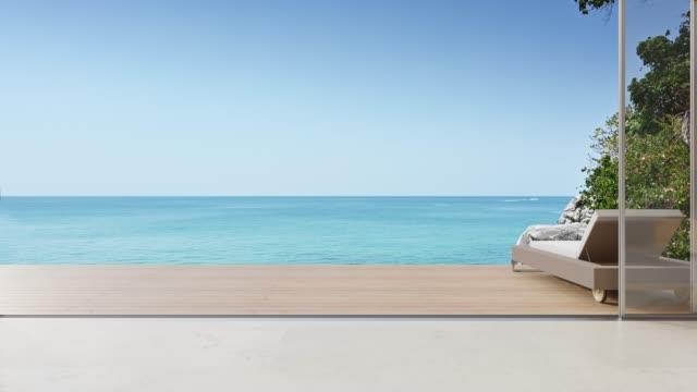 lounge chair on terrace near living room in modern beach house or luxury villa. - terrazza video stock e b–roll