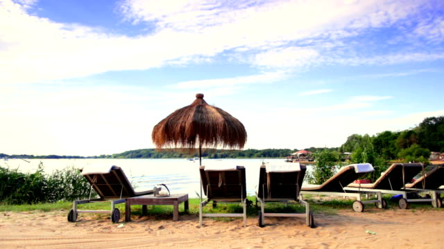 Lounge chairs and sunshades at lakeshore