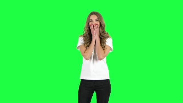 vídeos de stock e filmes b-roll de lovable girl smiling while looking at camera. green screen - teeshirt template