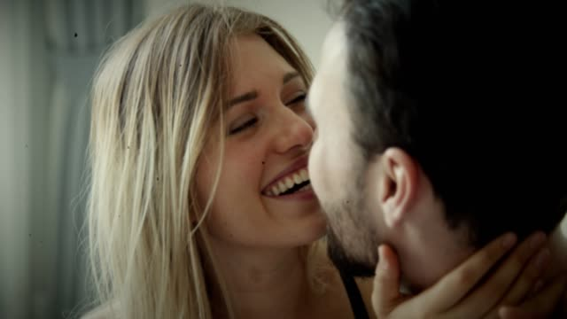 Love : Affectionate Handheld shot of happy caucasian young couple embracing in bedroom, 4K Resolution, Vintage Film Style kissing stock videos & royalty-free footage