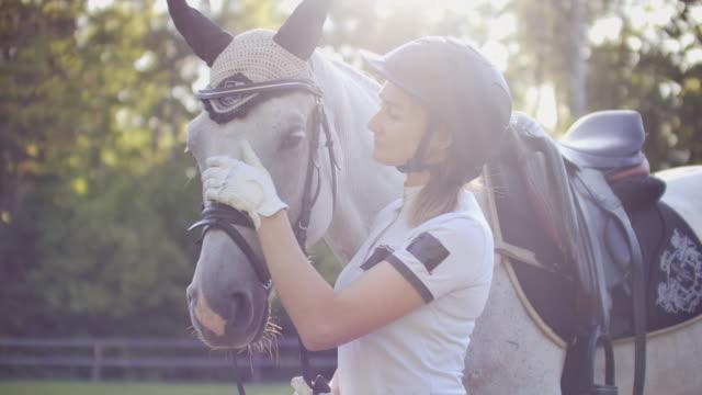 kärlek och omsorg från ryttare till hennes häst vän - hästhoppning bildbanksvideor och videomaterial från bakom kulisserna