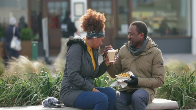 Love and Laughter A couple having a coffee and sharing chips outdoors on a bench. 50 54 years stock videos & royalty-free footage