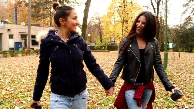Love and walk Two girls holding hands,walking and having nice conversation in the park. They are holding coffee and moving towards camera lesbian stock videos & royalty-free footage