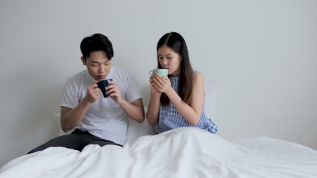 Love couple drink a coffee in the bed.