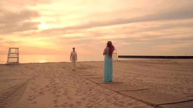 Love couple walking towards each other. Romantic evening on beach