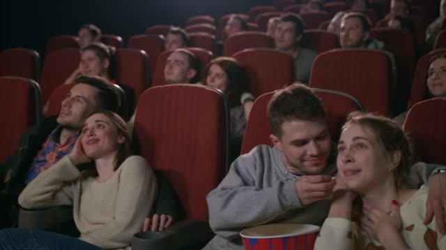 love couples watching movie at movie theater. young people eating popcorn - para aranżacja filmów i materiałów b-roll